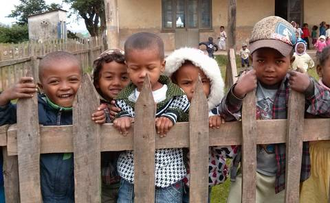 Malagasy children peering through a wooden fence in front of a house