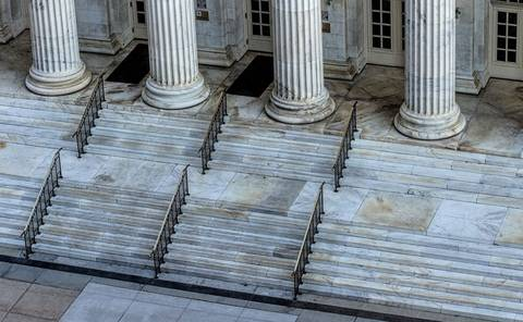 Steps leading to the pillars and doors of a court of justice.