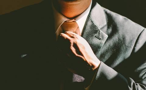 Close up of business man adjusting tie