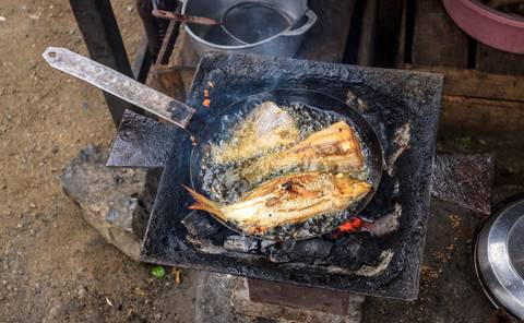 Roadside cooking in Madagascar: fried fish in oil on a simple coal stove.